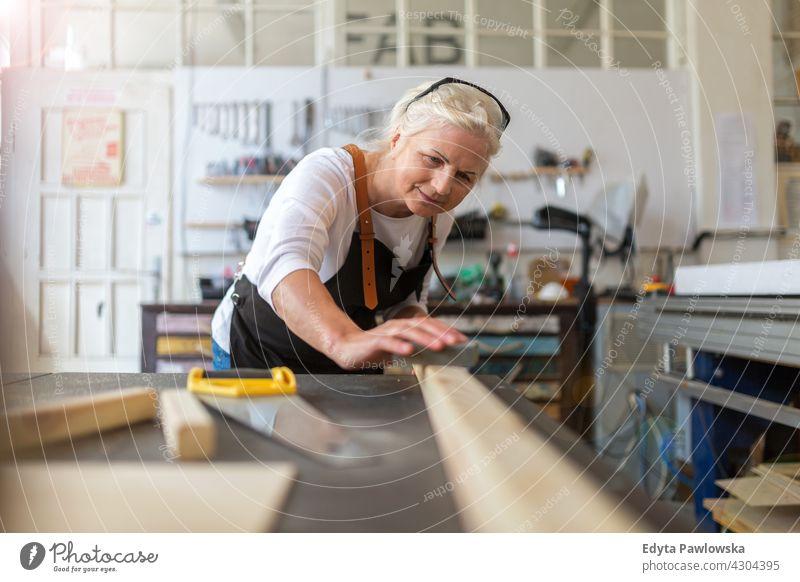 Ältere Frau bei Holzarbeiten in einer Werkstatt im Innenbereich Mechaniker Besitzer Beruf Dienst Kleinunternehmen Mitarbeiter Techniker Arbeitsplatz Arbeiter
