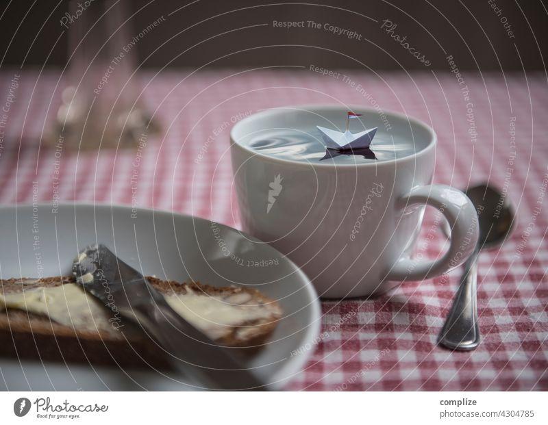 Kleines Papierschiff schwimmt in einer Tasse auf einem Frühstückstisch traumhaft Traumreise träumen Freiheit Miniatur klein Teller Basteln reisen Reise Urlaub
