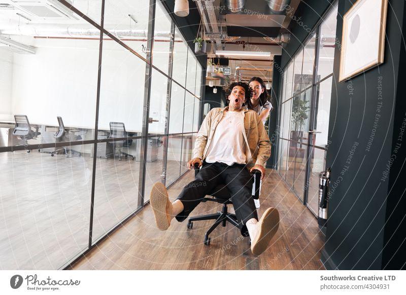 Junge Frau hat Spaß schieben Mann auf Stuhl entlang Gehweg in Großraumbüro jung Büro drücken Lachen Freitagsstimmung Montagsblues zu feiern Aufregung informell