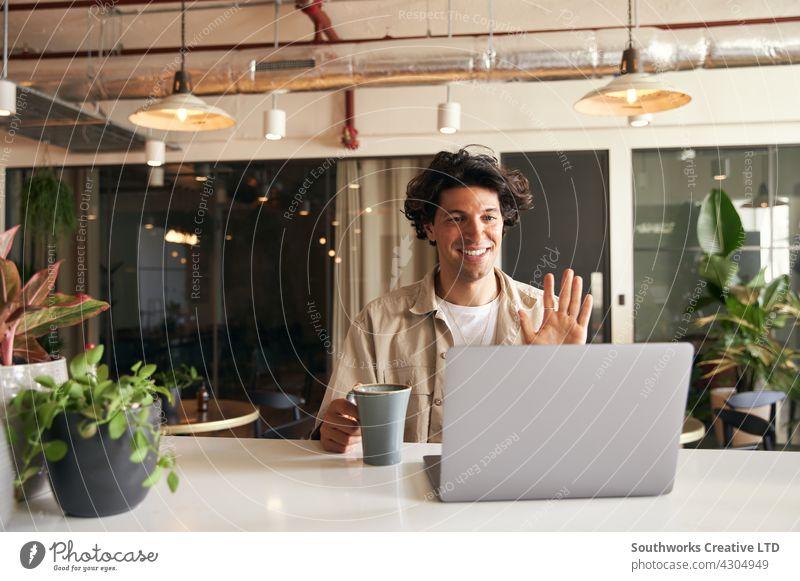 Junger Mann, der in einem Café arbeitet und ein virtuelles Meeting per Videoanruf auf seinem Laptop abhält jung Kaffeehaus Video-Chat Sitzung Fernarbeit
