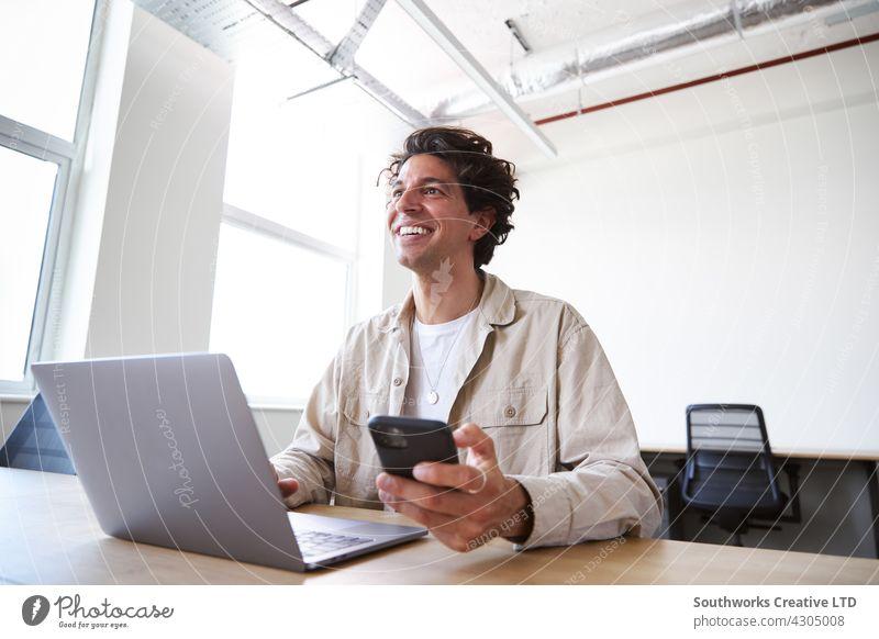 Junger Mann mit Laptop und Handy am Schreibtisch arbeiten auf Start-up-Unternehmen in Großraumbüro jung Büro Telefon Mobile Zelle Überprüfung Mitteilung modern