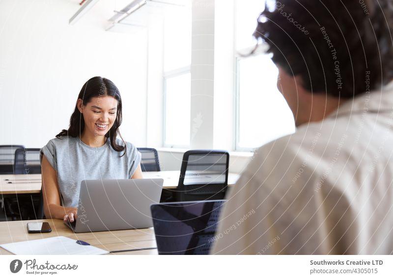 Junges Paar mit Laptops an Schreibtischen bei der Arbeit an einem Start-up-Unternehmen in einem gemieteten Großraumbüro Frau Mann jung Büro Sitzung informell
