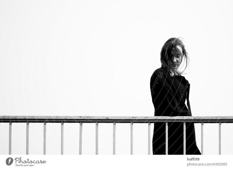 die junge Frau geht über eine Brücke und blickt nach unten langhaarig Wegsehen Mode 18-30 Jahre Haare & Frisuren feminin Lifestyle Beautyfotografie Erwachsene