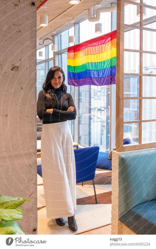 Brünette Frau ist stolz darauf, die LGBT-Gemeinschaft zu repräsentieren lesbisch lgbt Stolz allein Porträt brünett Lifestyle Vielfalt hispanisch bewundern Fahne