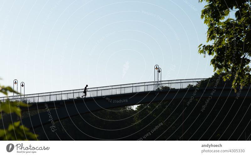 Silhouette eines Joggers auf einer Brücke Aktion aktiv Aktivität Erwachsener Athlet Sportler sportlich Leichtathletik Hintergrund hintergrundbeleuchtet