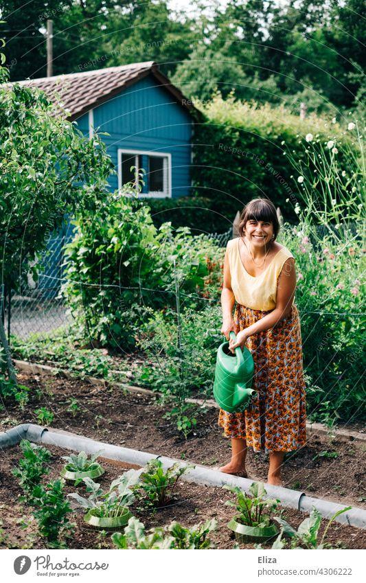 Frau gießt im Schrebergarten die Gemüsebeete mit einer Gießkanne Garten gießen Gartenarbeit Natur Sommer Gärtnerin bunt fröhlich lachen gute Laune Pflanzen