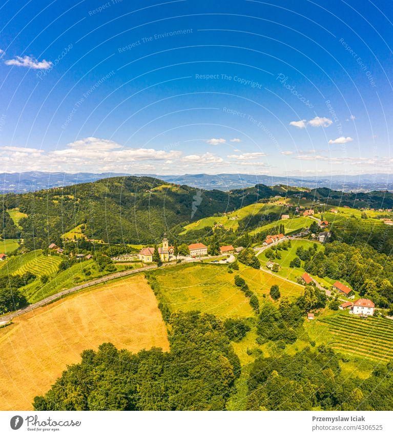 Luftaufnahme von grünen Hügeln und Weinbergen mit Bergen im Hintergrund. Österreich Weinberge Landschaft in Kitzeck im Sausal Sommer Natur Frühling Ackerbau