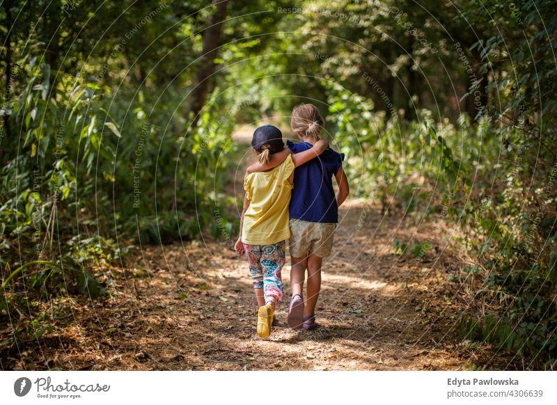 Junge Kinder laufen im Wald Freunde Zusammensein umarmend Schwestern Sommer Natur Glück im Freien Lifestyle sonnig Aktivität Fröhlichkeit jung Freizeit Mädchen