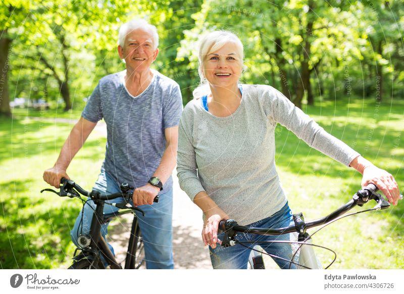 Senior Paar Reiten Fahrräder im Park Fahrrad Zyklus Senioren Rentnerin Rentnerinnen lässig im Freien Tag Kaukasier Fröhlichkeit zahnfarben Lächeln genießend