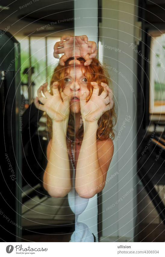 Porträt und Hände einer unheimlichen rothaarigen Frau, Gesichtsreflexion im Spiegel, weibliche Dualität, psychische Störung, unterbewusste Krise