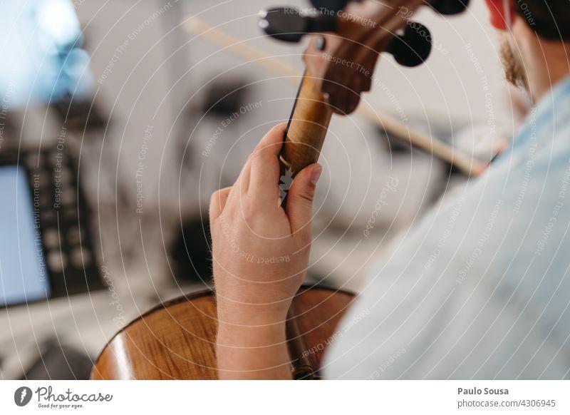 Nahaufnahme Hand hält ein Cello Musik Musiker Musikinstrument Innenaufnahme Farbfoto Saite Konzert Streichinstrumente Orchester Detailaufnahme musizieren Geige