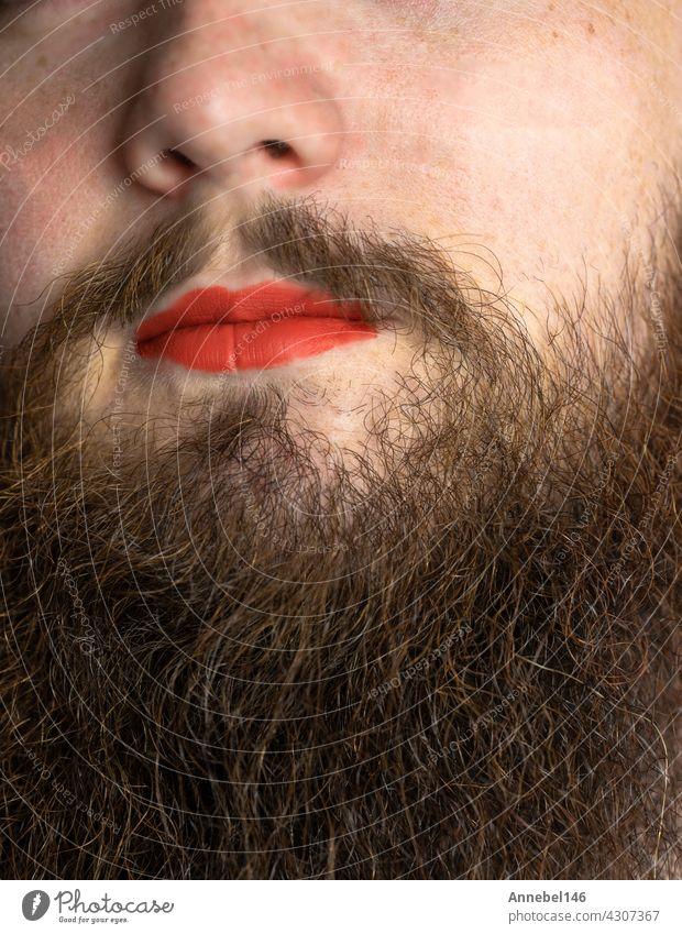 Bärtiger Mann mit rotem Lippenstift auf seinen Lippen, gut aussehend Stolz transgender Porträt lgbtq, transsexuelle Konzept Vollbart Make-up Mund Gesicht Model