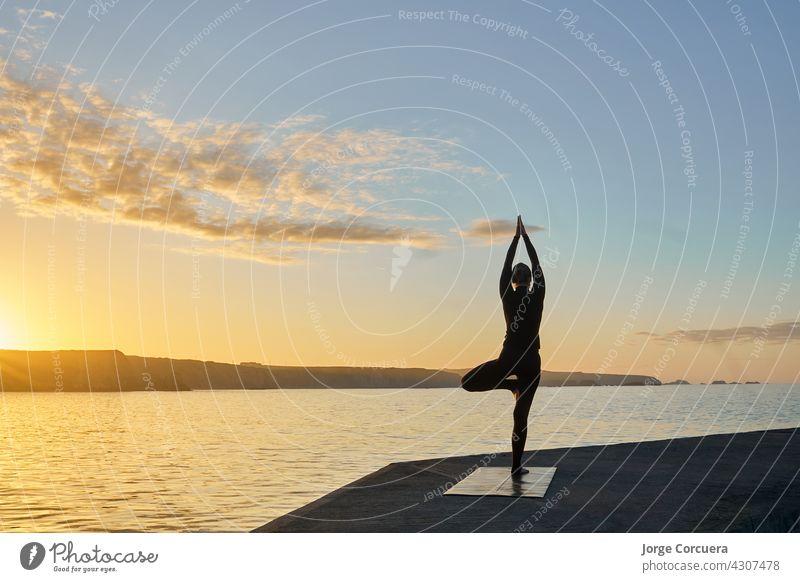 Silhouette der Frau übt Yoga im Gegenlicht jung praktizieren Fitness schlank Training passen Übung Pose Lifestyle Kaukasier positionieren Gesundheit Aktivität