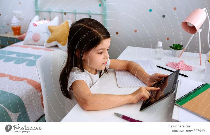 Mädchen lernt zu Hause mit Tablette und Maske auf dem Tisch studierend Schule zu Hause Heimunterricht Coronavirus covid-19 digitale Weisheit
