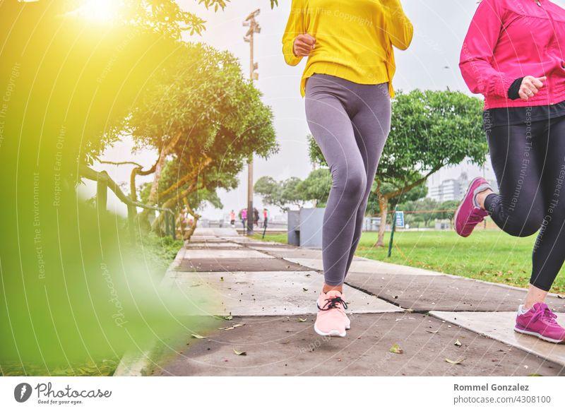 Multiethnische Frauen joggen auf der Straße Joggen Großstadt Übung Fitness Gesundheit Marathon sportlich Energie Textfreiraum Schuh Training Läufer Vitalität
