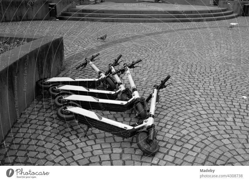 Umgestürzte E-Scooter für Touristen auf Kopfsteinpflaster in der Innenstadt von Frankfurt am Main in Hessen, fotografiert in neorealistischem Schwarzweiß Roller