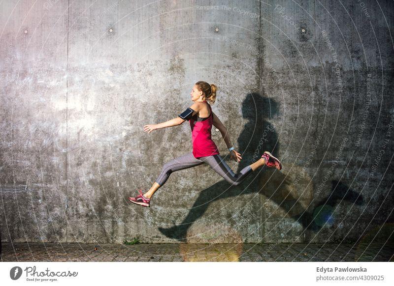 Junge Frau springt gegen graue Wand springend Aktion Gesundheit Tanzen Übung Flexibilität Jogger Läufer Joggen rennen Menschen jung Energie Bekleidung