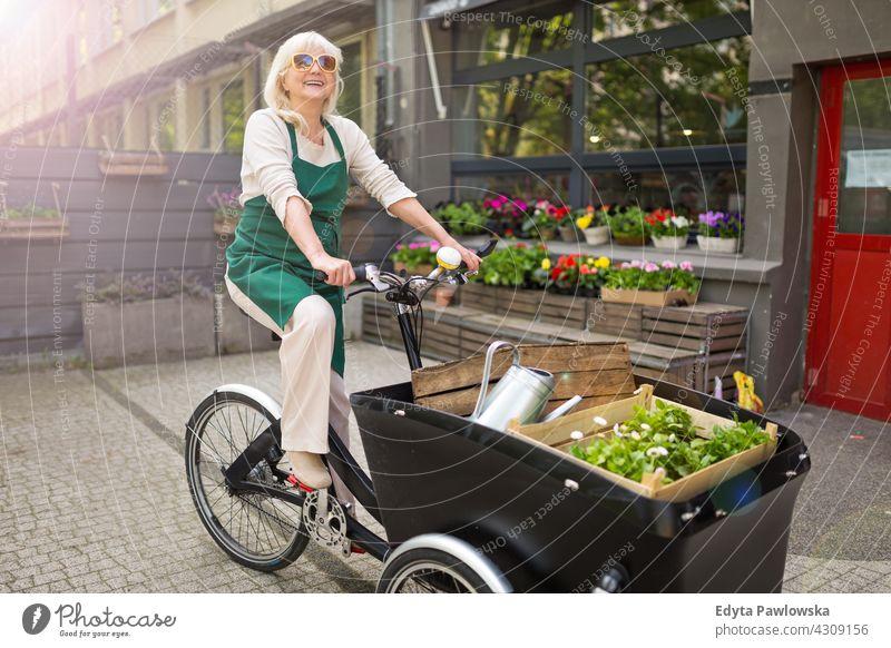 Glückliche Besitzerin eines Blumenladens mit Lastenfahrrad Fahrrad Fahrradfahren Verkehr Pendeln Lastenrad Versand Blumenhändler Menschen Erwachsener Senior
