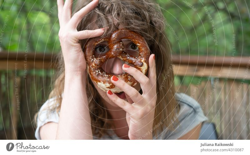 Frau mit Breze vorm Gesicht Brezel Backwaren lecker Bayern Oktoberfest Lebensmittel Teigwaren bayerisch Ernährung Frühstück Farbfoto Snack Vesper Essen salzig