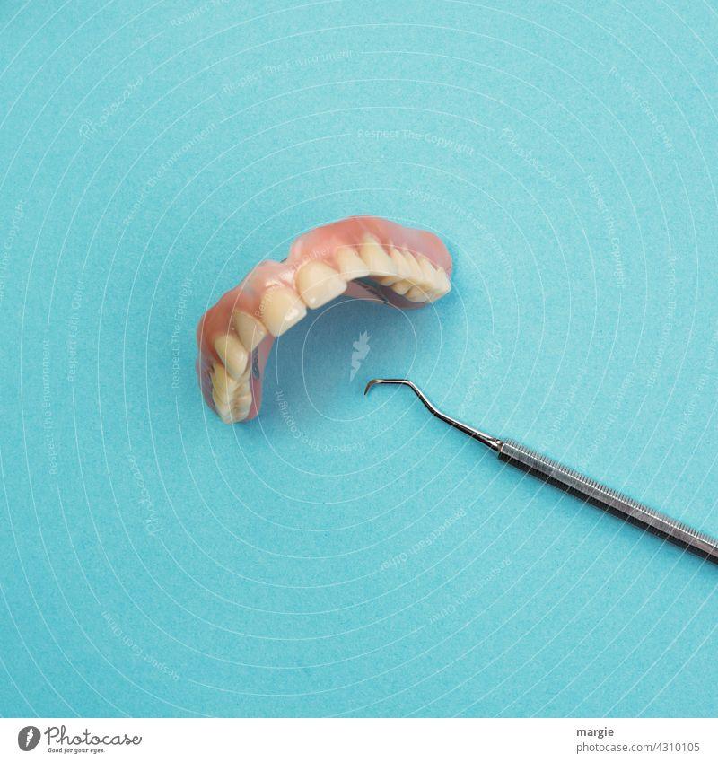 Künstliche Zähne, Gebiss mit Zahnreinigungsgerät Mund Nahaufnahme Detailaufnahme Model Kiefer Labor zahngesundheit senioren altern skuril Künstliche zähne