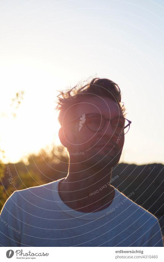 Gut gelaunter, junger Mann mit Brille und Zweitagebart im Gegenlicht Abendsonne Porträt maskulin Mensch Junger Mann Erwachsene Außenaufnahme Gesicht Gebüsch
