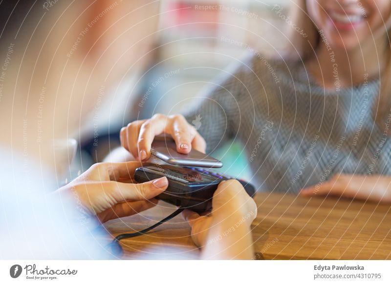 Kunde bezahlt mit Mobiltelefon im Cafe Kreditkartenleser Bank Banking Business kaufen Postkarte prüfen Chip Klient Code Belastung Finanzen Keyboard magnetisch
