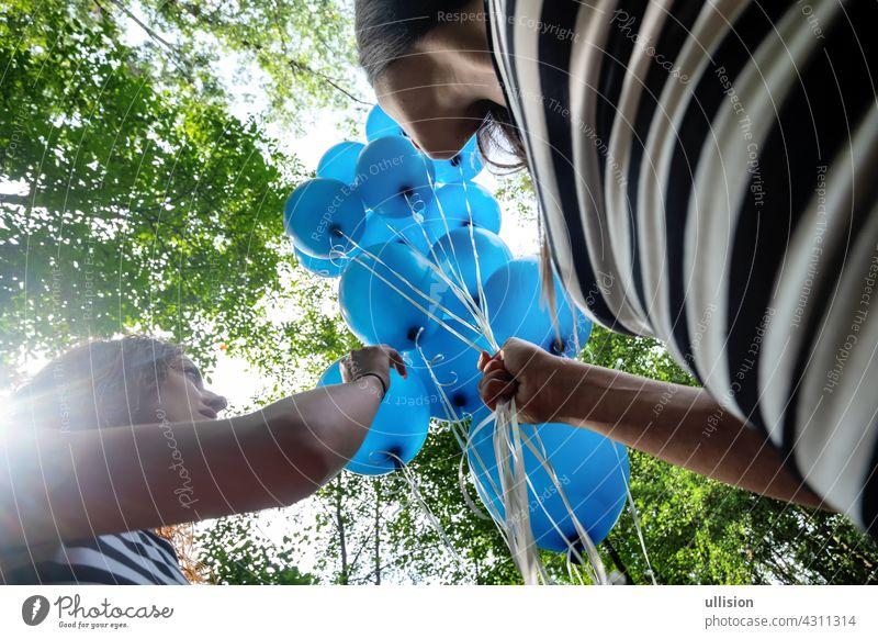 Blick von unten auf 2 blonde Frauen in schwarz-weiß gestreiften Kleinen mit einem Haufen blauer Luftballons Freunde Menschen Spaß Schönheit Erwachsener Ballons