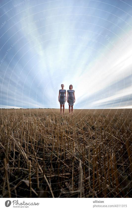 Zwei geisterhaft aussehende, unheimliche, junge Frauen in gestreiften Kleidern stehen vor dramatischem Himmel auf einem Stoppelfeld, Weitwinkel, Kopierraum.