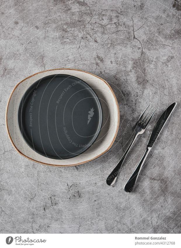 Leere Teller, Gabeln auf grauem Beton-Hintergrund. Draufsicht, Konzept Mockup. Löffel Studioaufnahme Reichtum romantisch Silber Attrappe speisend Servieren