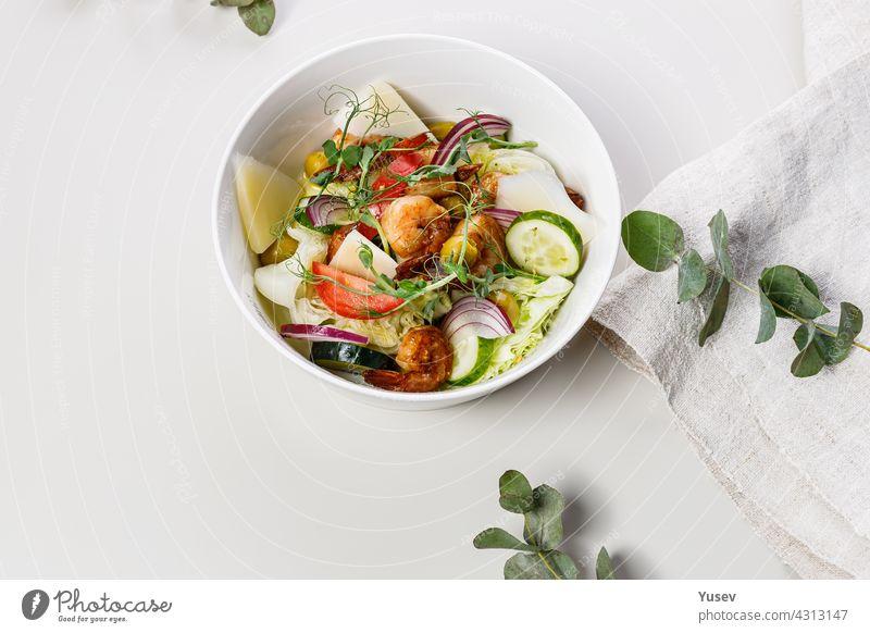 Close-up leckeren Sommersalat mit frischem Gemüse und Meeresfrüchten auf einem weißen Hintergrund. Gemüse der Saison, Garnelen und Ziegenkäse. Gesunde mediterrane Naturkost. Lebensmittel-Fotografie. Kopierraum