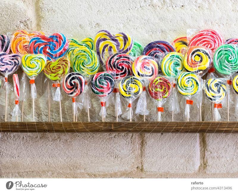 Bunte Spiral-Lollis im Verkaufsregal Lollipop Verwirbelung Bonbon Konditorei süß bunt Spirale gestreift ungesund vereinzelt kleben Saugnapf rot Zucker