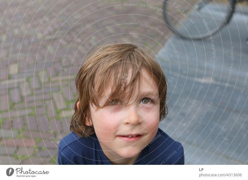 Junge mit gerötetem Auge, der in die Kamera blickt Lächeln Vertrauen Accessoire Haare & Frisuren Gesicht träumen verträumt nachdenklich Blick authentisch