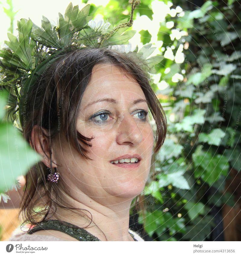Porträt einer lächelnden Frau mit braunen Haaren und blauen Augen im Halbprofil, im Hintergrund sind Pflanzen weiblich feminin Kopf Lächeln Ohrring Dame Blick