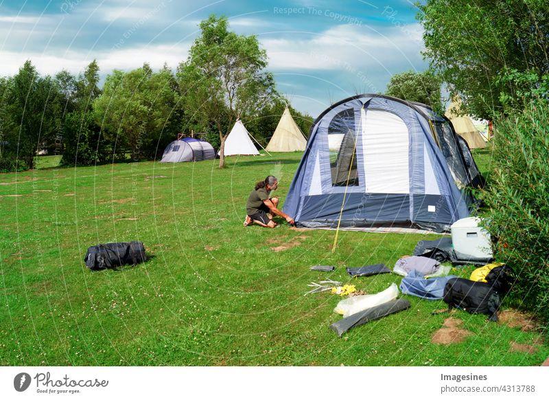 Zelten - Camping. Mann baut im Sommer ein Zelt auf einer Wiese auf aktiv Aktivität Erwachsene Abenteuer im Freien Lifestyle Campingplatz Landschaft Tag
