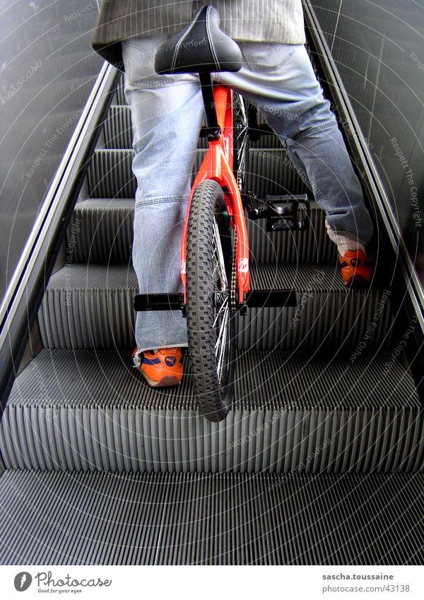 Xtrem-BMX-Sitzen auf Rolltreppe blau schwarz grau orange Schuhe sitzen stehen fahren Hose silber Freestyle Fahrrad BMX Rolltreppe Extremsport
