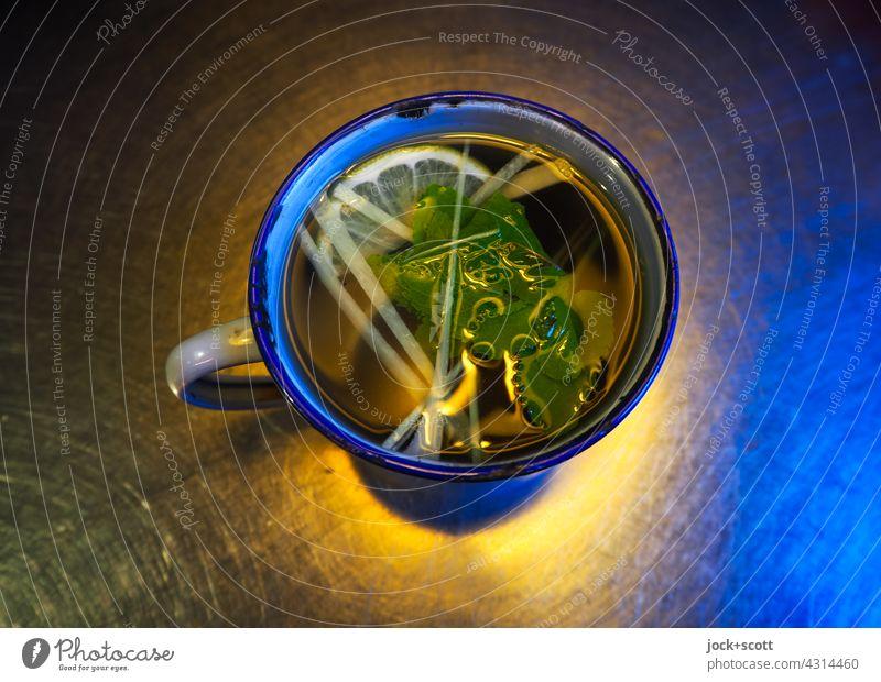 frischer fruchtiger Kräutertee ohne Zucker Tee Getränk Gesundheit Tischplatte Metall Beleuchtung farbig Pfefferminztee Vogelperspektive Wohlbefinden warm