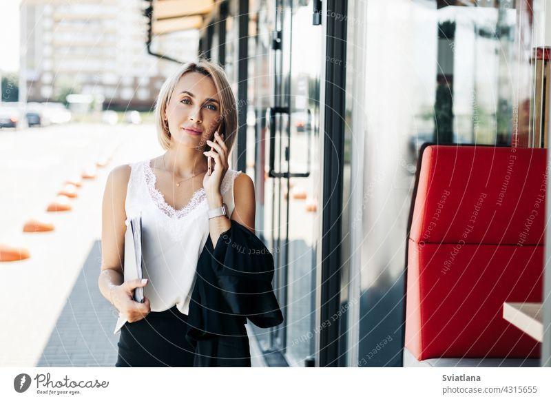 Eine schöne Geschäftsfrau, die in der Stadt telefoniert und einen Ordner mit Dokumenten hält Telefon Frau Straße Business Porträt sprechend Stehen Mädchen