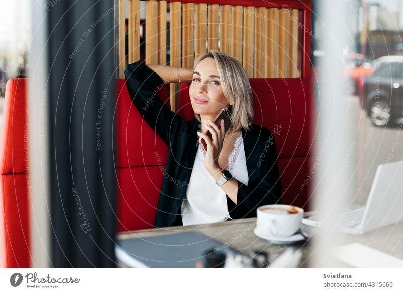 Ein attraktives Mädchen spricht mit einem Mobiltelefon und lächelt, sitzt allein in einem Café Telefon sprechend Frau Sitzen Tablette Geschäftsfrau Business