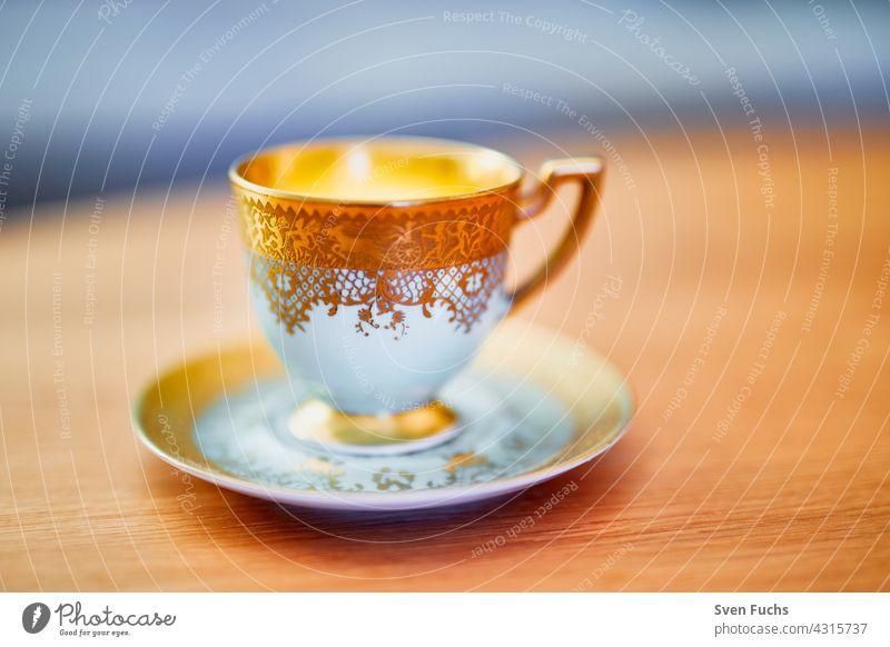Kaffeetasse und Untertasse mit Goldverzierung stehen auf einem Holztisch kaffeetasse goldrand geschirr mokka porzellan altmodisch edel festlich untertasse