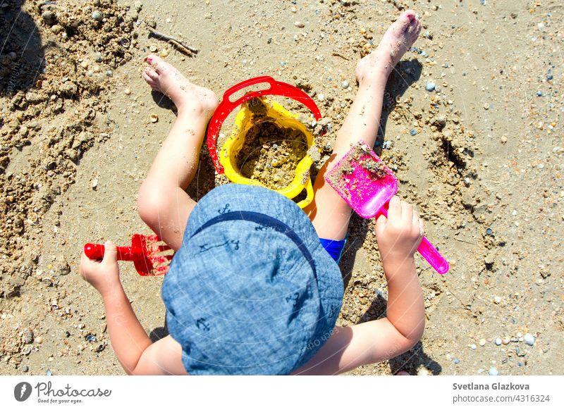 Kind spielt mit Sand, Schaufel, Eimer Strand Baby Burg oder Schloss Sommer wenig Gebäude spielen Kleinkind Urlaub Freude Freizeit Spielzeug Kindheit Sandburg