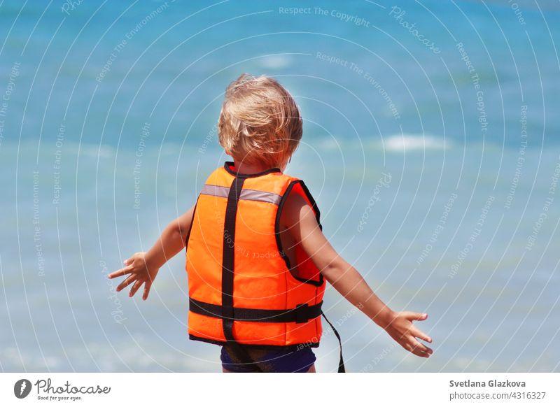 Sicherheit des Lebens Konzept. Kleine kaukasische Junge verwendet eine Schwimmweste auf einem Sommerstrand vor dem Hintergrund der Meereswellen.