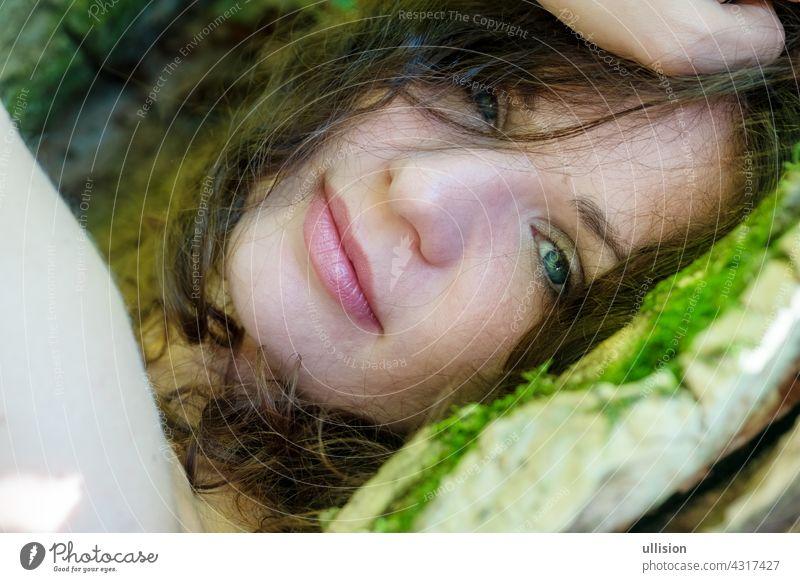 Porträt einer schönen dunkelhaarigen jungen sexy Frau liegt glücklich zufrieden im Bett von Moos im Wald mit in einem alten Weidenbaum mit nackten Schultern und tiefen Frieden in das Lächeln