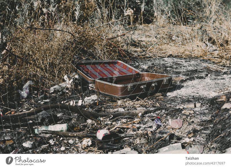 Ein alter, verwitterter Vintage-Koffer, der auf der Asche liegt Müll im Freien Konzepte Währung Zerstörung Finanzen Freiheit Ideen Lebensstile keine Menschen
