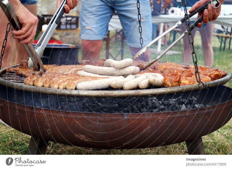 Barbecue - geselliges Beisammensein. Bratwurst und gegrilltes Fleisch, Steaks über den Kohlen auf dem Grill. Männer in kurzen Jeans grillen über einem Grillfeuer eine Auswahl an Fleisch- und Wurstwaren.