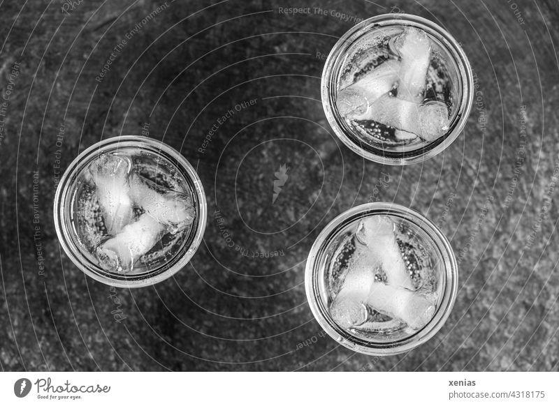 Drei runde Gläser mit Wasser und Eissticks in Schwarz-Weiß trinken drei Glas Getränk Flüssigkeit Trinkwasser Durst Wasserglas Mineralwasser Eiswürfel kalt