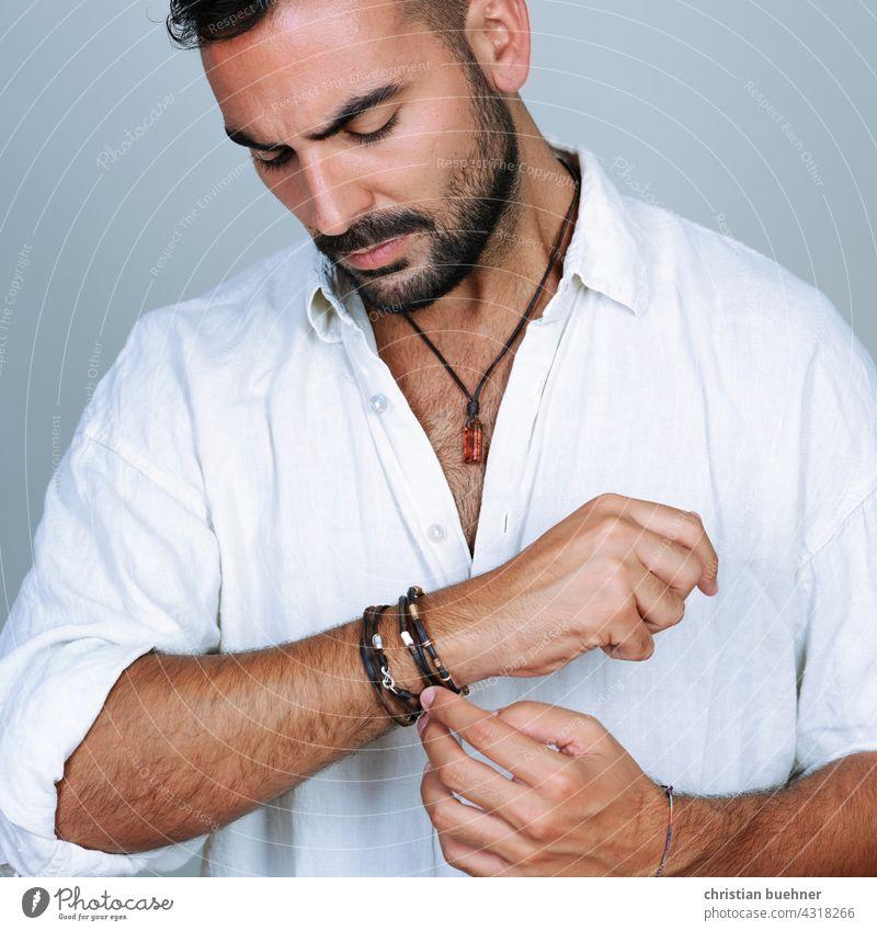 portrait eines jungen mannes  mit arm und halsschmuck studio halskette amber steine bernstein fashion mode armschmuck armbaender armreif silberschmuck