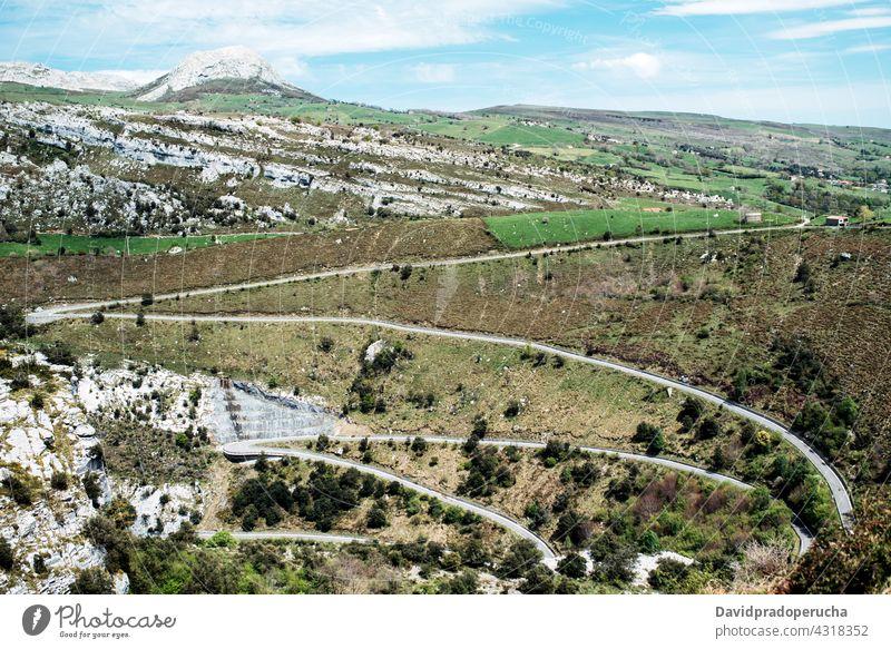 Sich schlängelnde Fahrbahn durch grüne Hügel im Hochland Serpentine Kurve Straße Berghang Berge u. Gebirge Natur Tal Geologie Gelände Asphalt Landschaft Route