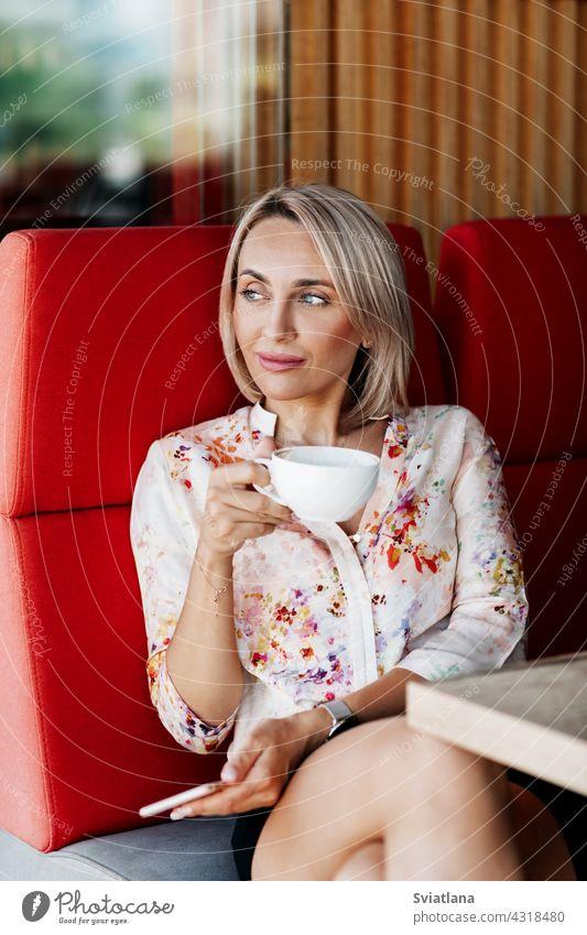 Ein schönes Mädchen trinkt Kaffee in einem Café und schaut nachdenklich in die Ferne Frau Mobile benutzend trinken Nachricht Beteiligung Menschen