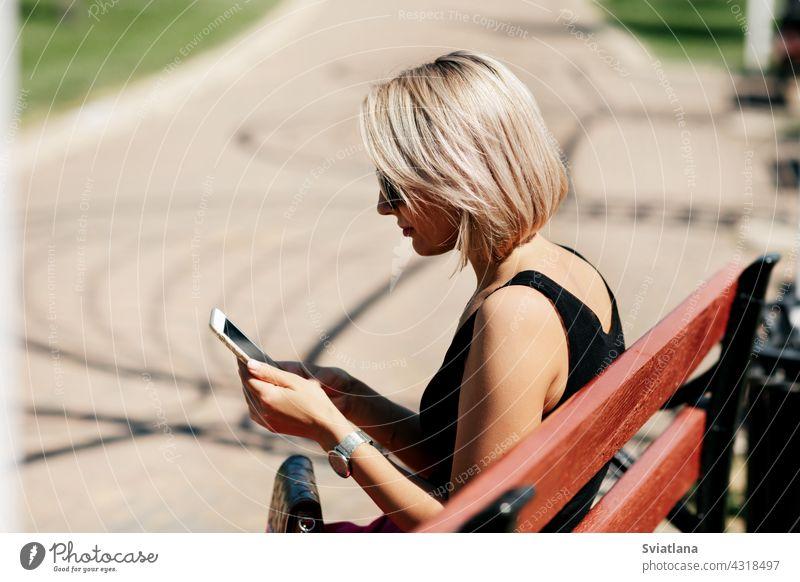 Eine junge Frau macht ein Selfie auf einer Parkbank sitzend, passt ihr Make-up und ihre Frisur an und betrachtet dabei ihr Spiegelbild auf dem Bildschirm Bank