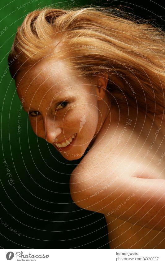 Rothaarige Frau zeigt Haut mit Sommersprossen und lächelt in die Kamera rothaarig Portrait nackt feminin Haare & Frisuren grün lachen lächeln Freude Schönheit